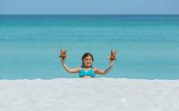 坐在白色沙子热带海滩的小快乐的微笑的女孩 图库摄影
