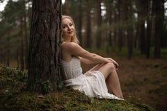 坐在白色礼服的森林若虫的美丽的年轻白肤金发的妇女在常青木头 免版税库存照片