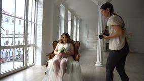 坐在白色peignoir的椅子和摆在摄影师的美丽的年轻孕妇 股票录像