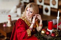 坐在的印度红莎丽服的美丽和肉欲的白肤金发的女孩 免版税库存图片