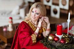 坐在的印度红莎丽服的美丽和肉欲的白肤金发的女孩 图库摄影