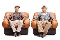 坐在皮革扶手椅子的两个年长人 免版税库存图片