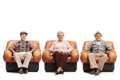 坐在皮革扶手椅子的两个年长男人和年长妇女 免版税库存照片