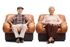 坐在皮革扶手椅子的前辈 免版税库存图片