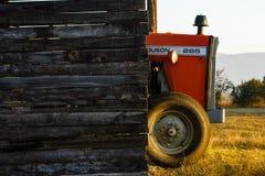 坐在盖子下的农用拖拉机在早期的阳光下 库存照片