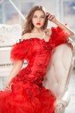 坐在盛大白色钢琴附近的红色礼服的美丽的妇女 库存照片