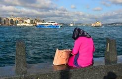 坐在码头的年轻回教妇女 免版税库存图片