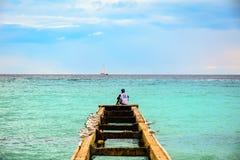 坐在码头顶部的一个人围拢由海鸥观察t 图库摄影