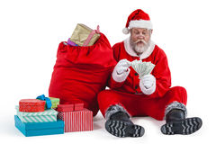坐在礼物旁边的圣诞老人计数货币笔记 免版税库存照片