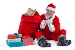 坐在礼物旁边的圣诞老人计数货币笔记 免版税库存图片