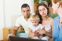 坐在社会工作者前面的父母和婴孩 库存照片
