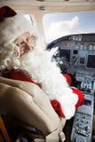坐在私人喷气式飞机的圣诞老人服装的人 库存图片