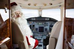 坐在私人喷气式飞机驾驶舱内的圣诞老人  免版税库存图片