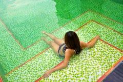 坐在私有游泳池的亚裔女孩 免版税库存图片
