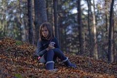 坐在秋叶的女孩在山毛榉森林里 免版税库存照片