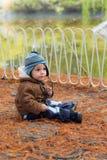 坐在秋天公园的小男孩 库存照片