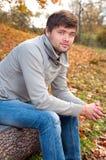 坐在秋天公园的愉快的年轻人 免版税库存照片