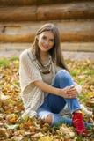 坐在秋天公园的蓝色牛仔裤的愉快的美丽的妇女 免版税库存照片