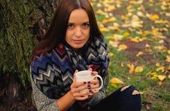 坐在秋天庭院里的美好女孩休息和饮用的咖啡 免版税库存图片