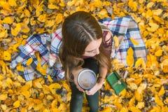 坐在秋天森林里的女孩,有一个杯子的格子花呢披肩的咖啡在手上 顶视图 免版税库存图片