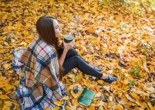 坐在秋天森林里的女孩,格子花呢披肩和饮料cofee的 图库摄影