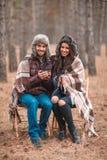 坐在秋天森林,饮用的热的茶和微笑里的愉快的夫妇 图库摄影