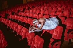 坐在空的观众席剧院的芭蕾舞女演员 免版税图库摄影