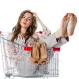 坐在空的购物拖钓的年轻美丽的深色的女孩 免版税库存照片