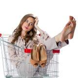 坐在空的购物拖钓的年轻美丽的深色的女孩 库存图片
