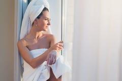 坐在窗口前的浪漫妇女和赞赏的日出或者日落与毛巾在她的顶头身体在浴以后 库存照片