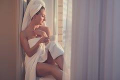 坐在窗口前的浪漫妇女和赞赏的日出或者日落与毛巾在她的顶头身体在浴以后 图库摄影