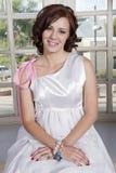 坐在窗口前面的年轻新娘 免版税库存照片