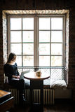 坐在窗口和用途膝上型计算机前面的桌上的少妇剪影 在线工作的女实业家 免版税库存图片
