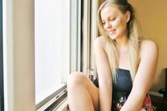 坐在窗口和逗人喜爱微笑附近的女孩 库存照片