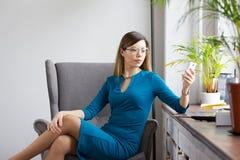 坐在窗口附近和看对智能手机的圆的玻璃的时兴的女商人 库存图片