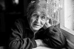 坐在窗口附近的哀伤的年长妇女 免版税图库摄影