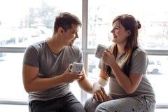 坐在窗口附近的年轻爱恋的夫妇 免版税库存照片