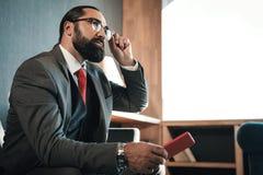 坐在窗口附近的有胡子的人戴着眼镜在他的酒店房间 免版税库存图片