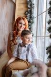 坐在窗口附近的母亲和儿子在有圣诞节装饰的屋子里 免版税库存图片