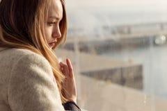 坐在窗口附近的美丽的哀伤的孤独的女孩失踪 免版税库存照片