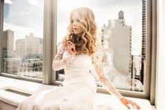 坐在窗口附近的美丽的时装模特儿新娘 免版税库存照片
