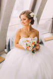 坐在窗口附近的年轻美丽的新娘和面纱特写镜头画象白色礼服的拿着花束 免版税库存图片