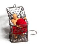 坐在笼子和拿着红心的行动象征在白色背景 爱和监禁的概念 库存图片