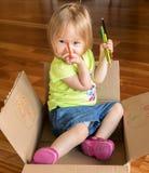 坐在箱子的年轻女婴 免版税库存照片