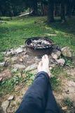 坐在篝火和休息附近的人 免版税库存图片