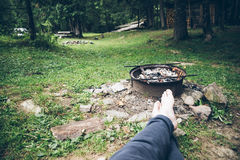 坐在篝火和休息附近的人 免版税库存照片