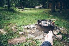 坐在篝火和休息附近的人 库存图片