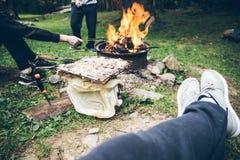 坐在篝火和休息附近的人 免版税图库摄影