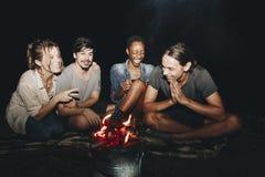 坐在篝火户外消遣休闲和友谊概念附近的小组年轻成人朋友 免版税库存照片