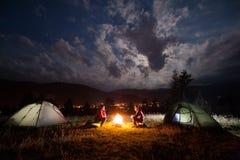 坐在篝火的女孩和人在帐篷附近在晚上 库存照片